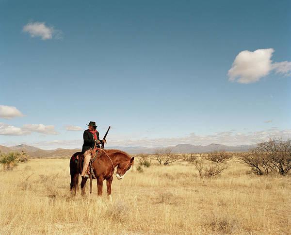 Rifle Photograph - Cowboy Riding On Horse by Matthias Clamer