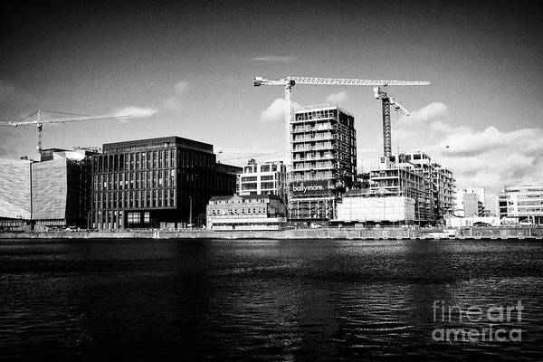 Wall Art - Photograph - cranes and new office developments at dublin landings in the docklands waterfront river liffey Dubli by Joe Fox