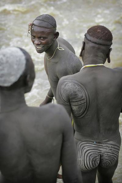 Buttocks Photograph - Decorated Suri Tribesmen Beside River by Timothy Allen
