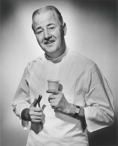 Gray Hair Photograph - Dentist Holding Pliers And Cup Posing by George Marks