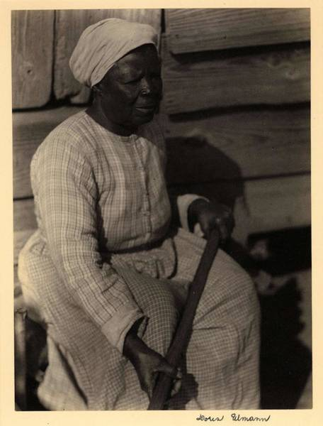 Wall Art - Painting - Doris Ulmann   1882-1934 , Black Woman In Turban And Dress, Seated Against Wood Building, Holding Lo by Doris Ulmann