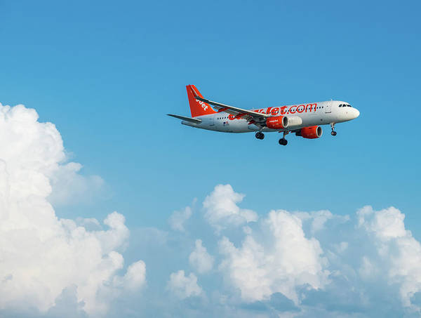 Photograph - Easyjet Airbus A320 Flying By In White Clouds And Blue Sky by Iordanis Pallikaras