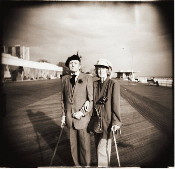 Heterosexual Couple Photograph - Elderly Couple On Boardwalk, Portrait by Rob Goldman