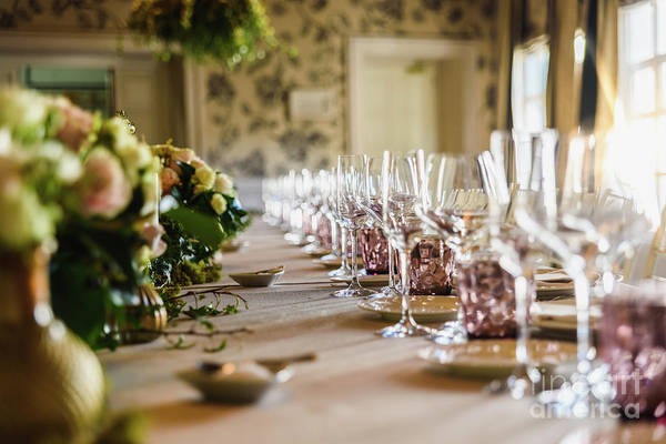 Photograph - Elongated Table With All The Cutlery Elegantly Arranged And Beautiful Centerpieces Ideal For Decorating A Wedding. by Joaquin Corbalan