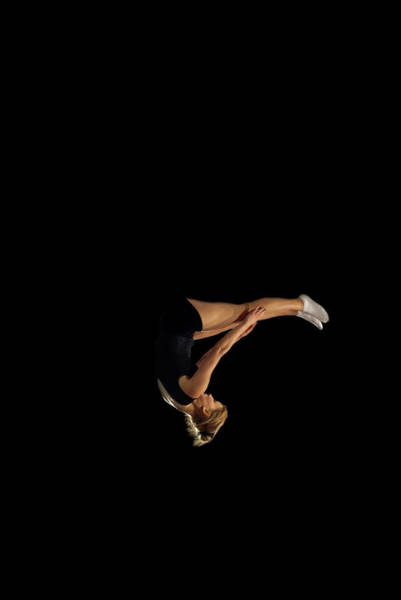 Upside Down Photograph - Female Gymnast Upside Down Mid Flight by Peter Muller