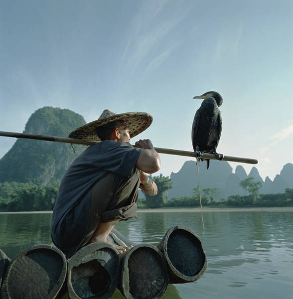 Photograph - Fisherman Sitting On Bamboo Raft With by Martin Puddy