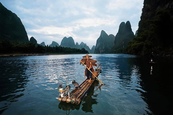 Raft Photograph - Fisherman Standing On A Wooden Raft In by Redchopsticks