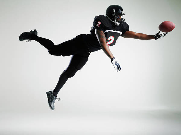 Football Helmet Photograph - Football Player Leaping In Mid Air To by Thomas Barwick