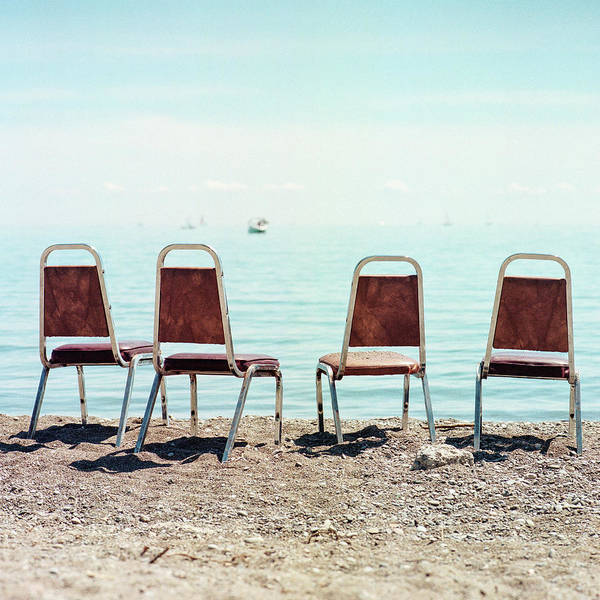 Wall Art - Photograph - Four Empty Chairs By The Water by Christian Senger