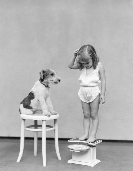 Scale Photograph - Girl Standing On Scales, Looking Down by H. Armstrong Roberts
