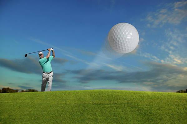 Golf Photograph - Golfer On Grassy Hill Hitting Golf Ball by Guy Crittenden