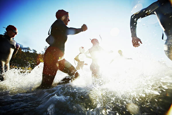 Senior Adult Photograph - Group Of Triathletes Running Into Water by Thomas Barwick
