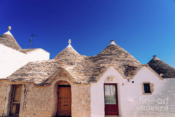 Photograph - Houses Of The Tourist And Famous Italian City Of Alberobello, With Its Typical White Walls And Trulli Conical Roofs. by Joaquin Corbalan