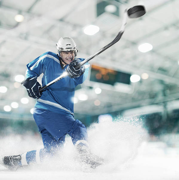 Helmet Photograph - Ice Hockey Player Shooting Puck by Bernhard Lang