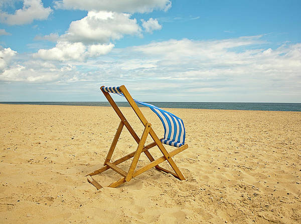 Deck Chair Photograph - Lawn Chair Blowing In Wind On Beach by Ashley Jouhar