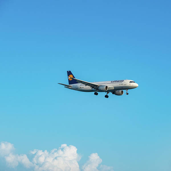 Photograph - Lufthansa Airbus A320 Flying By In White Clouds And Blue Sky by Iordanis Pallikaras