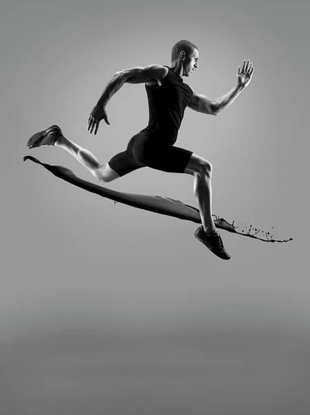 Endurance Race Photograph - Male Athlete Running Above Liquid Splash by Jonathan Knowles
