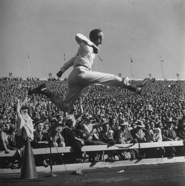 Photograph - Male Cheerleader Leaping High Into Air by Loomis Dean