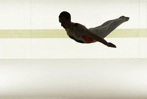 Practice Photograph - Male Gymnast Performing Somersault In by Romilly Lockyer