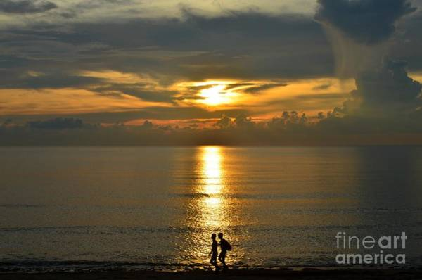 Photograph - Male Swimmers Walking Along The Sunset In Photograph by Christopher Shellhammer