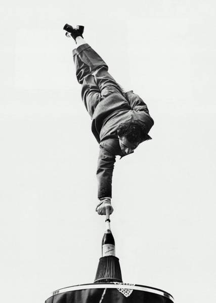 Upside Down Photograph - Man Balancing On Fingertip On Champagne by Hulton Archive