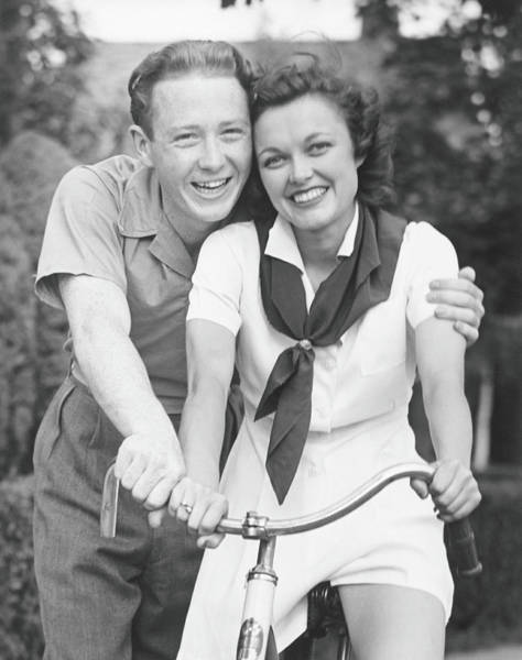 Heterosexual Couple Photograph - Man Embracing Woman Sitting On Bike by George Marks
