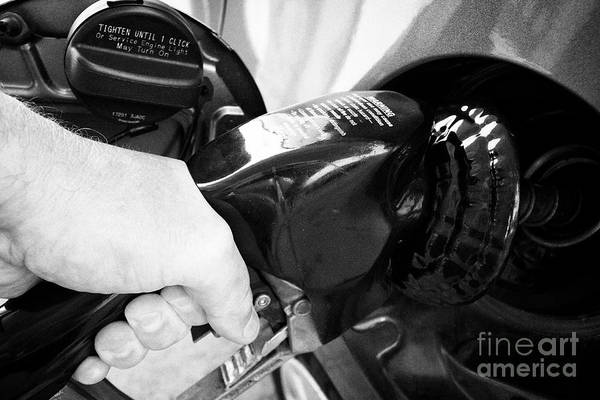 Wall Art - Photograph - man filling up car with regular gasoline from pump in Jacksonville Florida USA by Joe Fox
