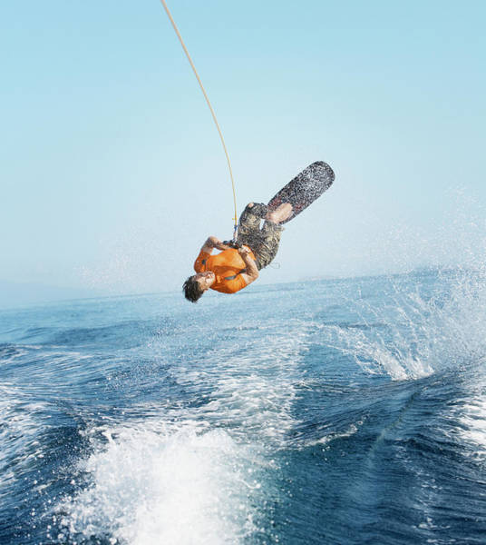 Upside Down Photograph - Man Performing Wakeboarding Stunt At Sea by Paul Bradbury