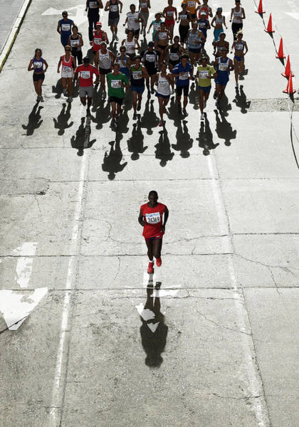Wall Art - Photograph - Man Running In Front Of Pack In Marathon by Michael Blann