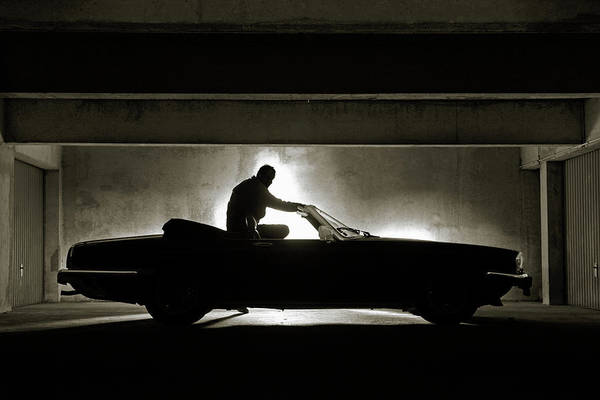 Parking Garage Photograph - Man Sitting On His Car by Bertrand Demee