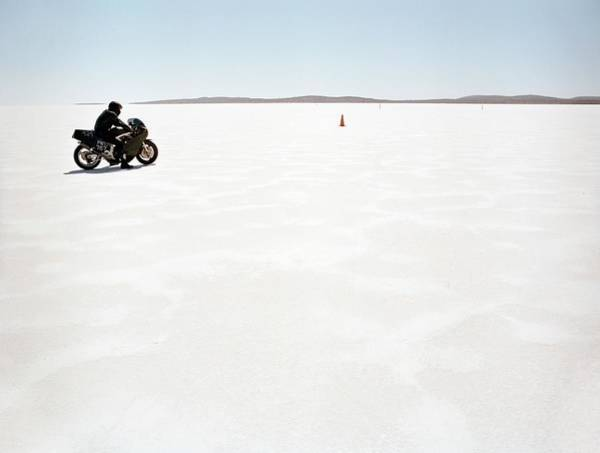 Motorcycle Racing Photograph - Man Sitting On Motorcycle On Salt Flat by Tobias Titz
