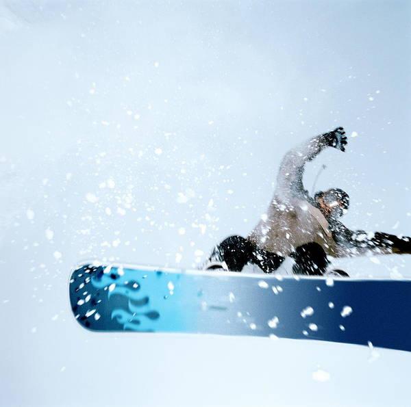 Photograph - Man Snowboarding, Mid-jump. Low Angle by Martin Barraud