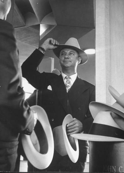Man Trying On Hats At Nieman Marcus Depa Art Print by Nina Leen