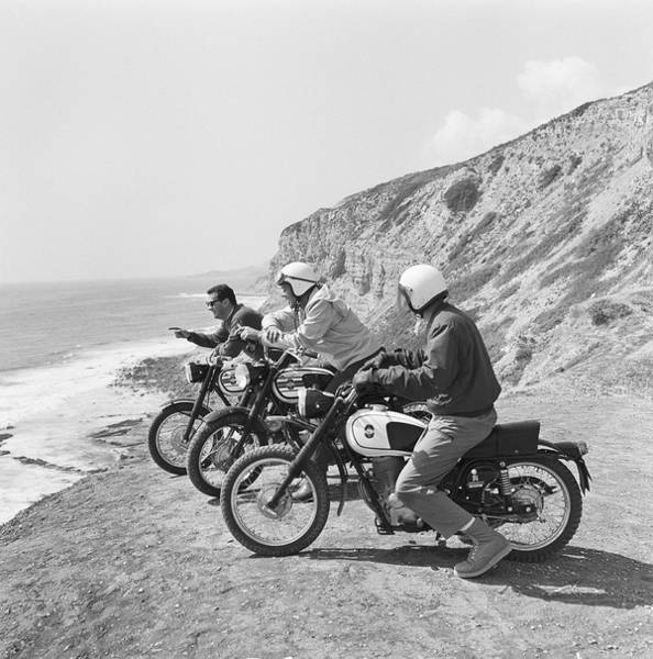Helmet Photograph - Men Sitting On Motorbike Along Coastline by Tom Kelley Archive