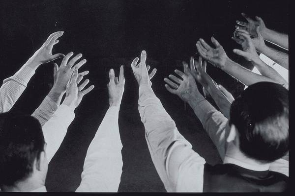 Human Hand Photograph - Mens Hands Reaching Out Into Blackness by Archive Holdings Inc.
