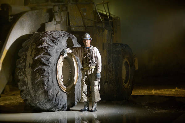 Wall Art - Photograph - Mining Worker Standing Beside Tyre In by Tyler Stableford