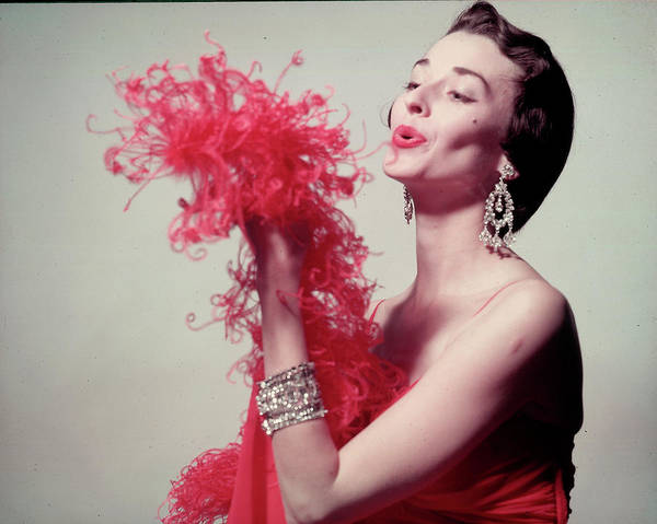 Photograph - Model Blowing On Red Feather Boa & Weari by Gjon Mili