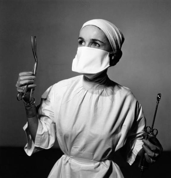 Black Cap Photograph - Nurse Holding Up Surgical Tools B&w by Hulton Archive