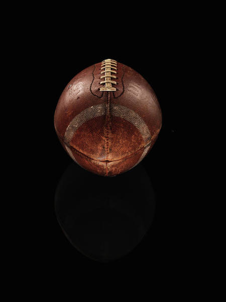 American Football Photograph - Old Football On Black Background by Alexander Nicholson