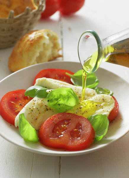 Wall Art - Photograph - Olive Oil Pouring On Caprese Salad In by Westend61