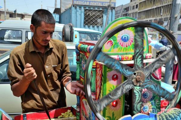 Photograph - Pakistani Man Tends Colorful Sugar Cane Juice Machine Karachi Pakistan by Imran Ahmed