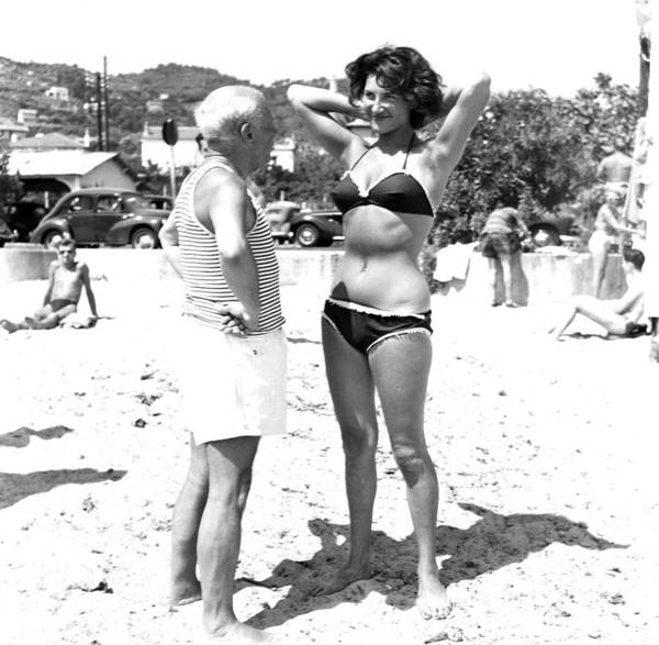 Smiling Photograph - Picasso And Bikini-clad Woman On The by Hulton Archive