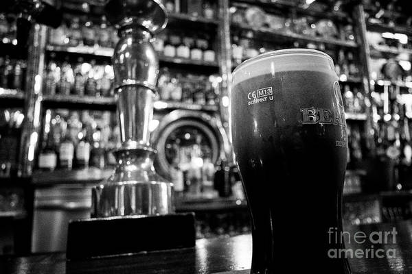 Wall Art - Photograph - pint of beamish stout settling in The Long Hall victorian pub one of the oldest pubs in Dublin repub by Joe Fox