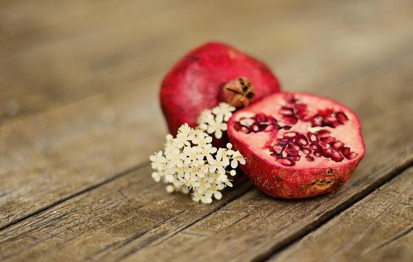 Wood Photograph - Pomegranate And Flowers On Tabletop by Anna Hwatz Photography Find Me On Facebook