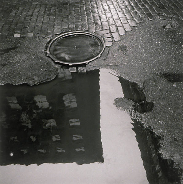 69fc218f6 Manhole Wall Art - Photograph - Puddle On Street With Building by Henri  Silberman