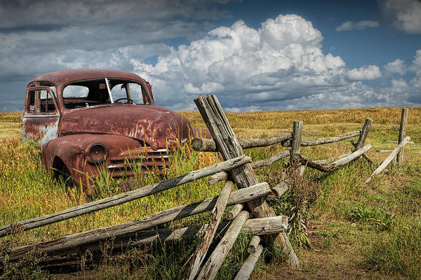 Photograph - Rusted Vintage Automobile In A Rural Landscape Behind Old Wooden Log Fence by Randall Nyhof