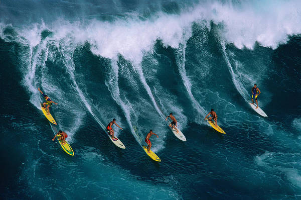 Motion Photograph - Seven Surfers Riding Large Wave by Warren Bolster