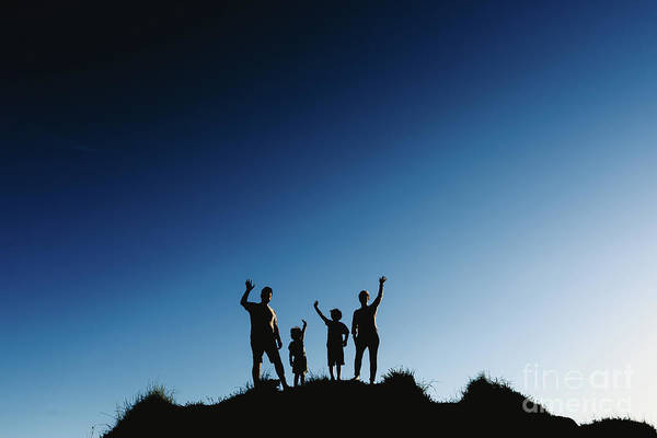 Photograph - Silhouette Of A Happy Family On Top Of A Hill Waving At Sunset. by Joaquin Corbalan