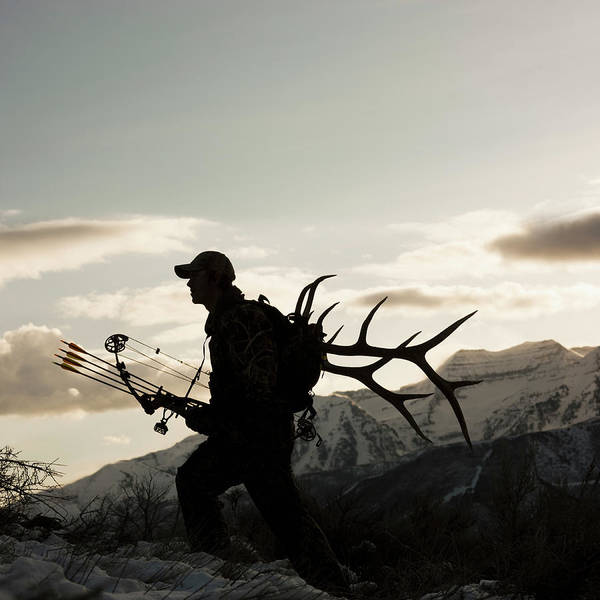 Archery Photograph - Silhouette Of Hunter Hiking With Elk by Mike Kemp Images