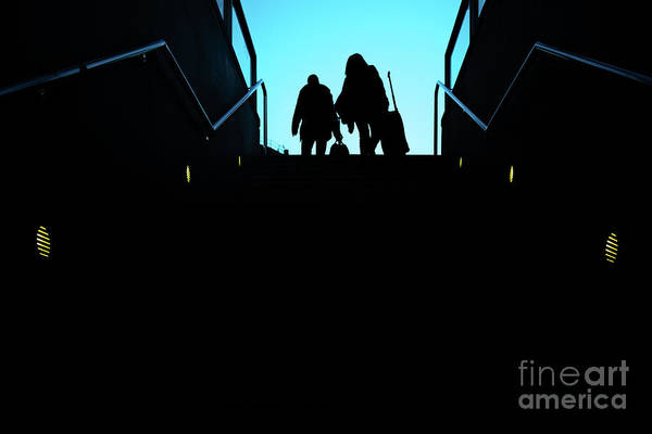 Photograph - Silhouette Of Two Passengers With Their Suitcases Trolley Climbing A Ladder by Joaquin Corbalan